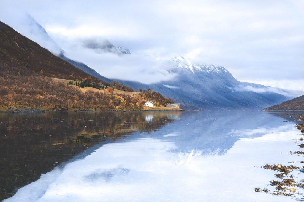 Norjan Lyngenin Alpit lokakuussa. Norjan maalaismaisema, vuoristo, kirkas vuonon vesi.