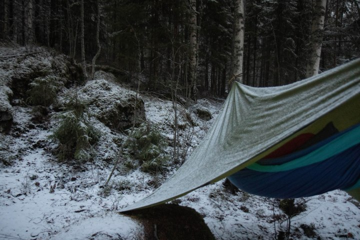 Yö ulkona talvella riippumatossa Etelä-Konneveden kansallispuistossa Enonrannan laavun lähellä. Yöllä satanut lumi jäi kevyenä tarpin pinnalle.